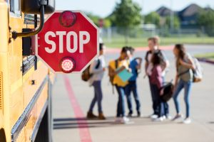 A group of young school students stand near the bus and talk together.