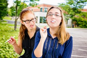 Teenage girl teaching an unsure friend how to smoke using an e-cigarette.