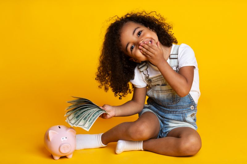 Little girl with piggy bank and cash