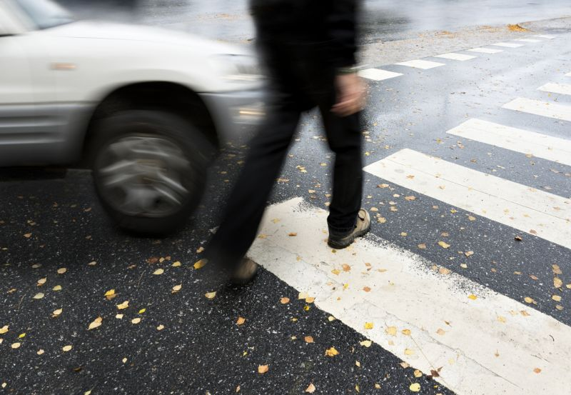 Man on pedestrian crossing in danger of being hit by a car