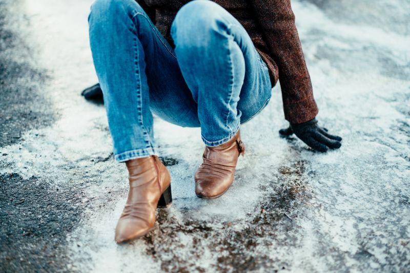 Woman fallen down on icy sidewalk
